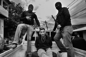 Gli agenti di polizia vanno in giro mascherati per evitare violenze e ritorsioni contro loro o i loro cari. In questa foto due agenti portano con sé un sospetto spacciatore dopo un raid a Tegucigalpa. (Sean Sutton/Panos Pictures for The Washington Post)